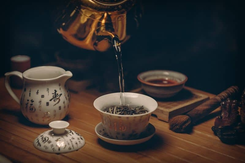 pouring water from kettle into tea cup