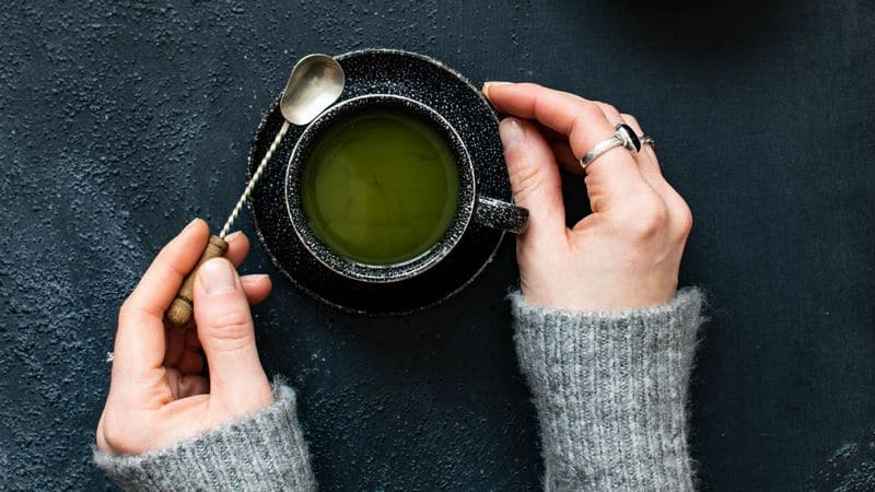 Woman's arms holding tasty green tea