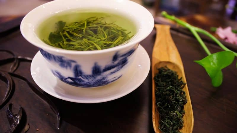 A cup of green tea with leaves
