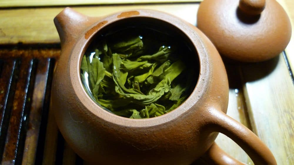 Green tea leaves in clay pot