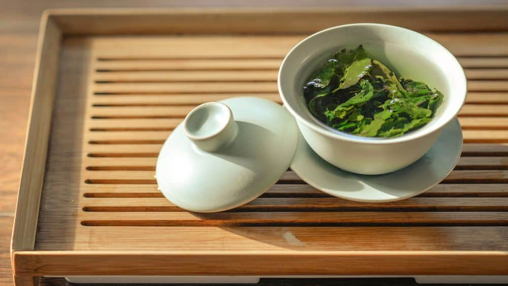 Green tea leaves steeping in a cup